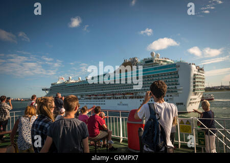 Isle of Wight ferry passengers waving at a luxury cruise ship sailing out of Southampton, Hampshire, UK - Stock Photo