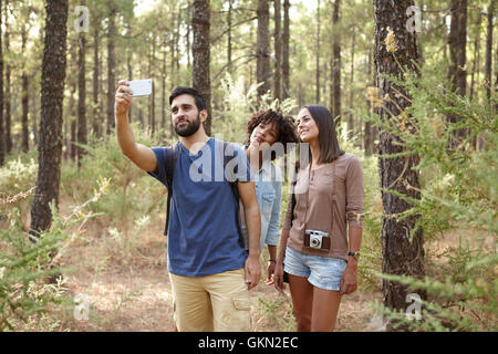 Three friends hiking through a pine tree forest in the late afternoon shadows and taking selfies in front of a tree - Stock Photo