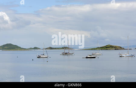 Sailing boats at anchor in a sheltered harbour on a still summer day. , Islay, Inner Hebrides, Argyll, Scotland, - Stock Photo