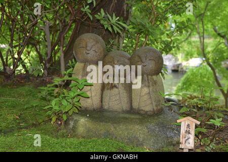 Cute little statues praying in a zen garden in Japan - Stock Photo
