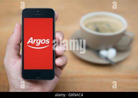 A man looks at his iPhone which displays the Argos logo, while sat with a cup of coffee (Editorial use only). - Stock Photo