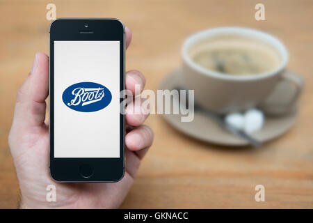A man looks at his iPhone which displays the Boots logo, while sat with a cup of coffee (Editorial use only). - Stock Photo