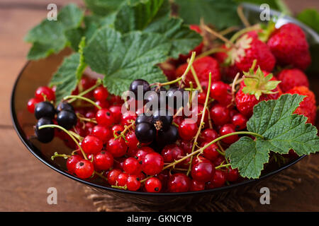 Plate with fresh berries (strawberries and currants) on dark wooden background - Stock Photo