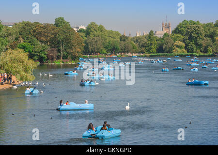 Hyde Park serpentine lake, tourists in boats enjoy a summer afternoon on the Serpentine in Hyde Park, London, UK. - Stock Photo