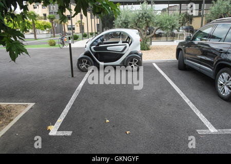 Small micro car a Renault Twizy electric car badly parked,or blatantly ignoring marker lines in Limoux hospital - Stock Photo