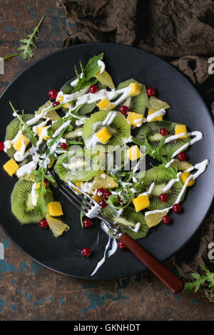 Fruit salad with sliced kiwi, mango, orange, red currant, rucola and yogurt dressing, on black plate with fork and - Stock Photo