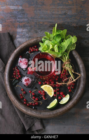 Ingredients for making lemonade Ice cubes, red currant berries, lime, lemon and mint, served with glass of juice - Stock Photo