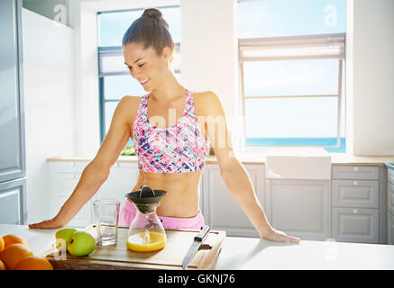 Shapely healthy young woman making fresh juice in her kitchen from a variety of fruit on the counter , copy space - Stock Photo