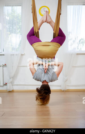 Back view of woman doing yoga in hammock otdoor - Stock Photo