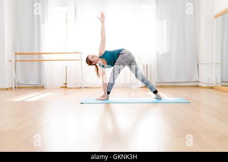 young yoga instructor in utthita trikonasana pose with