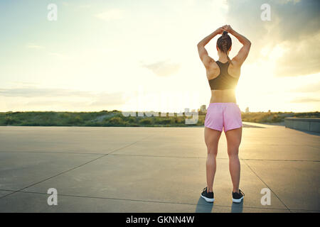 Fit muscular young woman standing on a rural road facing the rising sun doing stretching exercises with her arms - Stock Photo