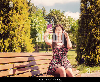 young girl making selfie sitting on a park bench on sunny summer day - Stock Photo