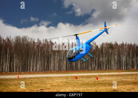 The aircraft - the small blue helicopter at competitions makes flight at low height on cloudy sky background. - Stock Photo