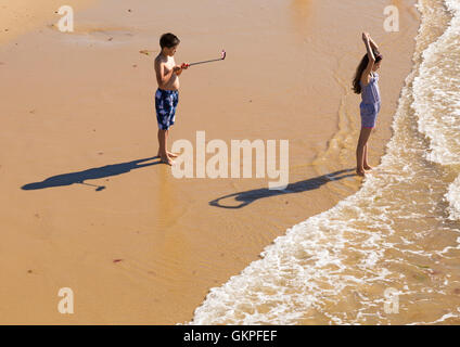 Bournemouth, Dorset, UK 23 August 2016. Couple taking a photo with mobile phone on selfie stick on a hot sunny day - Stock Photo