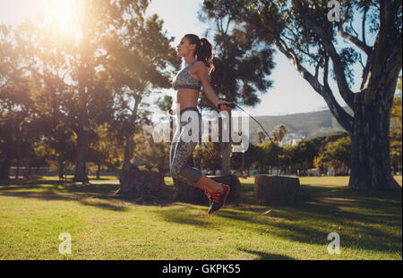 Full length portrait of fit young woman skipping with a jump rope in the park on a summer day. - Stock Photo
