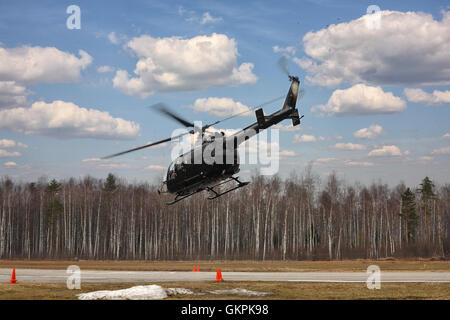 The aircraft - the black helicopter at competitions makes flight at low height on cloudy sky background. - Stock Photo