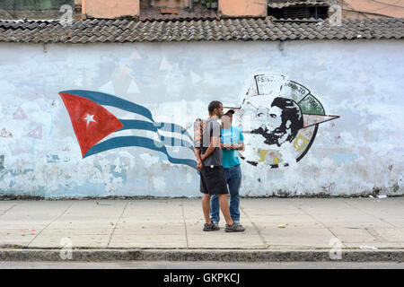 Two Cuban men standing in front of a a revolutionary mural on a wall in Old Havana (La Habana Vieja), Cuba - Stock Photo