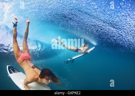Active girls in bikini in action - surfers with surf board dive underwater under breaking big ocean wave. Extreme - Stock Photo