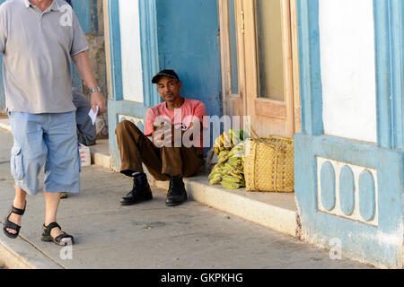 A Cuban man sits on a step selling bananas in Trinidad, Sancti Spiritus province, Cuba - Stock Photo