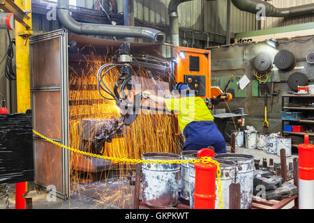 workman grinding and cutting away cast metal components from its 'casting' tree. - Stock Photo