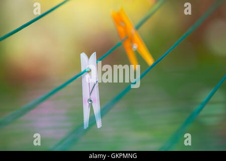 Brightly coloured clothes pegs on a rotary washing line. - Stock Photo