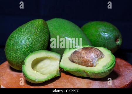 Ripe avocado cut in half on a black table. Close-up - Stock Photo