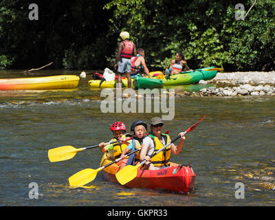 Mother with young children going on a canoeing adventure on the Herault river in the Cevennes region, southern France - Stock Photo