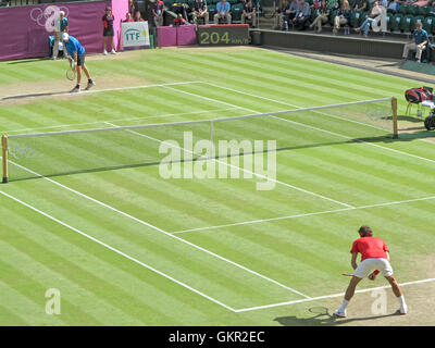 Wimbledon, England. August 2nd, 2012. Roger Federer and John Isner during their singles matches at the summer Olympics - Stock Photo