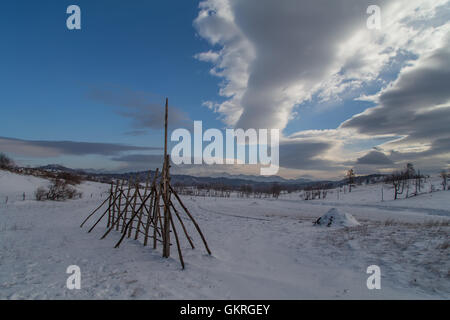 Snowy landscape with hayrack with beautiful clouds - Stock Photo