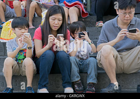An Asian family sitting on the steps at the public library in Downtown Flushing, Queens, NYC, all using their cell - Stock Photo