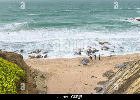 Holidaymakers on a beach in a small cove on The Headland in Newquay, Cornwall. - Stock Photo