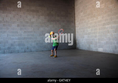 7 year old boy playing tennis in an empty half built shop. - Stock Photo