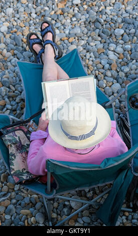 senior female person reading book sitting in seat on shingle beach - Stock Photo
