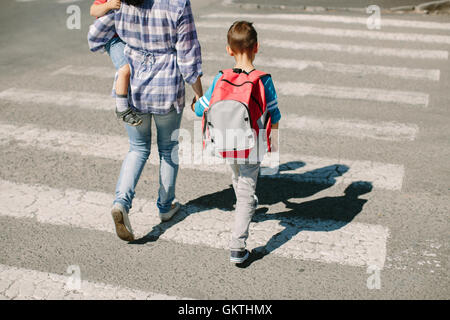 Mother and her children crossing road on way to school. Mother with her sons walking across zebra crossing. - Stock Photo