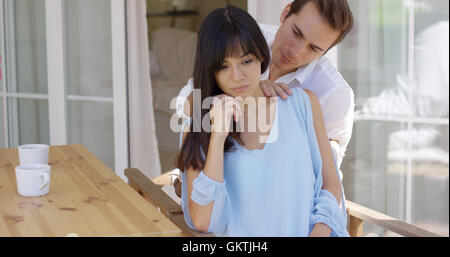Man trying to comfort sad woman at table - Stock Photo