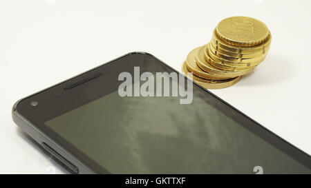 Mobile phone with coins - Stock Photo