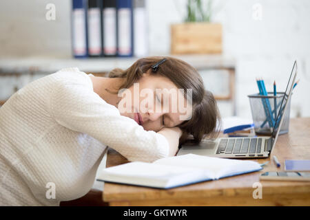 Portrait of young woman lying on the table in front of laptop, sleepy, tired, overworked or lazy to work. Attractive - Stock Photo