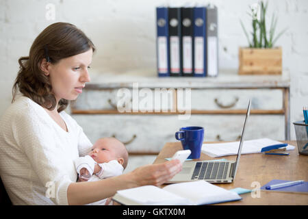 Portrait of young business mom holding her newborn cute babe while working in home office interior, looking at cellphone - Stock Photo
