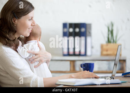 Side view portrait of happy casual young business mom holding her newborn cute babe while working on laptop in home - Stock Photo