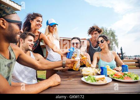 Teenage happy friends having picnic party outdoors - Stock Photo