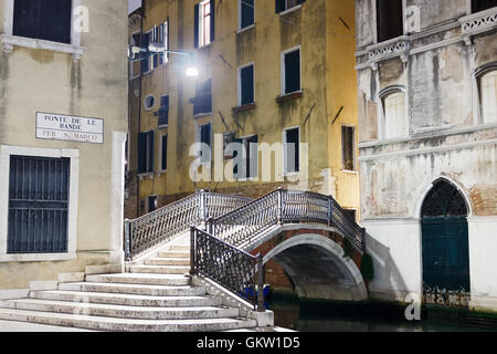 VENICE, ITALY - MARCH 31, 2016: A decorative railed bridge with marble steps over a venetian canal, illuminated - Stock Photo