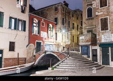 VENICE, ITALY - MARCH 31, 2016: A venetian street corner with a bridge over a canal and old buildings illuminated - Stock Photo