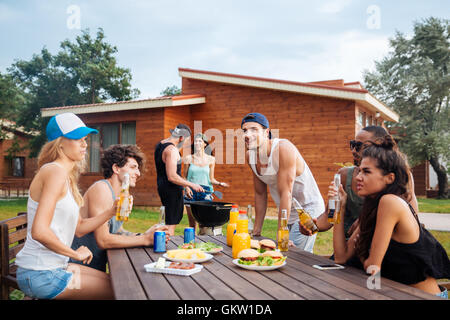 Happy group of young cheerful friends having fun at picnic outdoors - Stock Photo