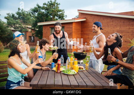 Group of happy young people laughing and having fun on barbeque party - Stock Photo