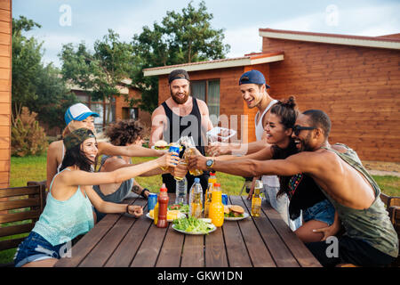 Group of happy young people celebrating and having outdoor party - Stock Photo