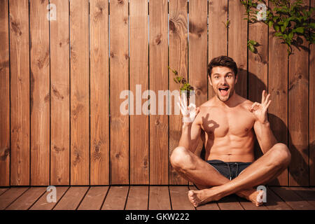 Handsome young smiling man sitting and showing okay sign over wooden background - Stock Photo