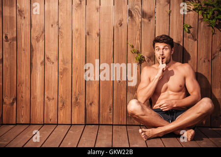 Handsome young excited man sitting and showing silence gesture over wooden background - Stock Photo