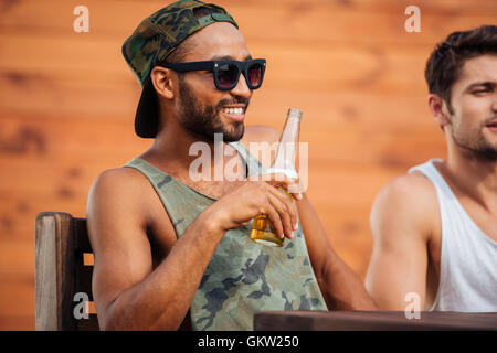 Young african man holding beer bottle and having fun time with friends outdoors - Stock Photo