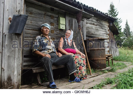beautiful mature russian couple have fun outside of their house in village. The woman clothed in a scarf keeps the - Stock Photo
