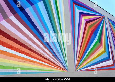 Brightly colored geometric designs painted on the exterior wall of a building, prism style art - Stock Photo